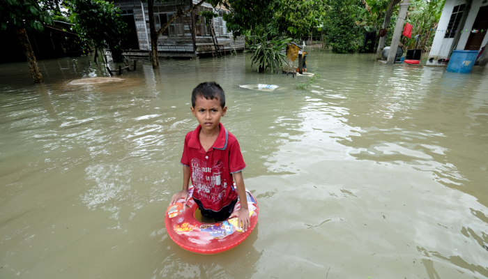a boy stands in flood waters in front of his home in Malaysia.