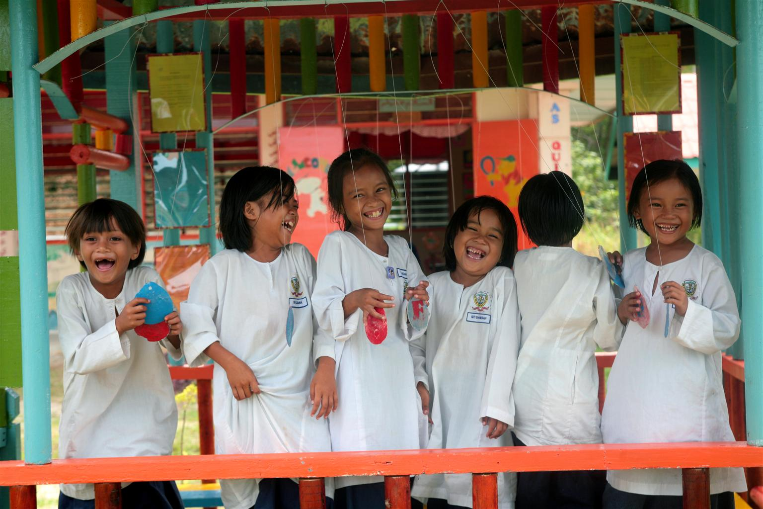 Children from the Bajau ethnic group laugh and play during recess at Timbang Island Primary School, on Timbang Island in the state of Sabah. UNICEF provides rural schools in Sabah with supplies and teacher training, part of efforts to improve literacy among rural and indigenous children.  In September 2007 in Malaysia, gaps in education, health care and other services persist, particularly in rural areas, where rates of poverty remain high. Among the rural poor are indigenous ethnic groups collectively known as the Orang Asli, whose cultural and geographic isolation from the urban majority contribute to extremely high dropout rates. Some 80 per cent of Orang Asli children fail to complete secondary school. In response, UNICEF is working with the Government to expand education in remote villages and rural communities. UNICEF also supports programmes that encourage school retention by incorporating Orang Asli folk tales and storytelling techniques into the curriculum. In all parts of the country, health care for women and children is also inadequate. Despite an overall decline in HIV/AIDS rates, there has been a fourfold increase new HIV infections among women, and the number of children affected or orphaned by the disease continues to grow. UNICEF is supporting HIV/AIDS awareness among girls and women, as well as outreach programmes for injecting drug users, the largest contributors to the spread of HIV/AIDS. In a separate initiative, UNICEF is working with the Ministry of Health to promote the detection of autism in toddlers and young children.